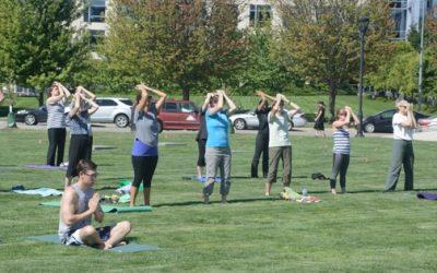 men and women practicing qigong outside in grass