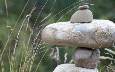 stacked rocks with grass in background