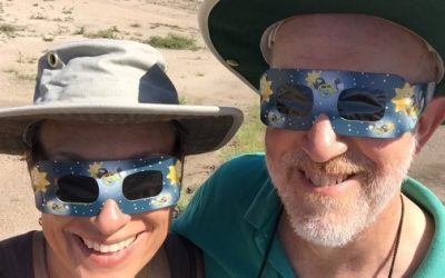 man woman eclipse glasses with hats