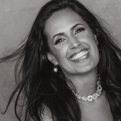 lady with dark hair smiling in black and white