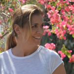 lady in white shirt with pink flowers in background smiling